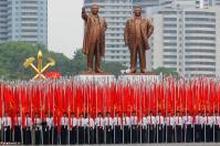 Students carrying party flags stand under statues of former North Korean leaders Kim Il Sung and Kim Jong Il at the beginning of a mass rally and parade in Pyongyang. REUTERS/Damir Sagolj
