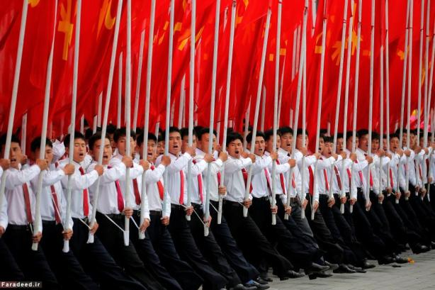Students carrying party flags and shout slogans as they march past North Korean leader Kim Jong Un during a mass rally and parade in the capital's main ceremonial square in Pyongyang